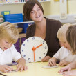 Stock Photo: Teacher helping schoolchildren learn to tell time in primary cla