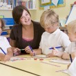 Schoolchildren and their teacher in a primary class — Stock Photo