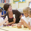 Schoolchildren learning numbers with their teacher - Stock Photo