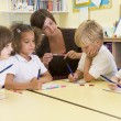 Schoolchildren and their teacher in a primary class - Stock Photo