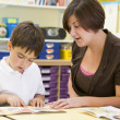 A schoolboy and his teacher reading in a primary class — Stock Photo