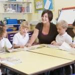 školáky a jejich učitele čtení v hlavní třídě — Stock fotografie