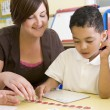 Primary school teacher helping boy learn numbers - Stock Photo