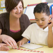 Primary school teacher helping boy learn numbers -  