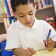 Boy learning to write numbers in primary class - Stockfoto