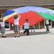 Young children playing with a parachute in a playground - Stock Photo