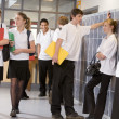 Stock Photo: High school students by lockers in school corridor