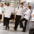 High school students by lockers in the school corridor - Stock Photo