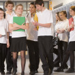 Teenage boys clustered around a girl at school — Stok fotoğraf