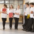 Teenage boys watching girls walk down a school corridor — Stock Photo