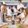 A teacher eating lunch with his students in the school cafeteria - Stock Photo