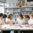 Schoolchildren studying in school library - Stock Photo