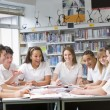 Schoolchildren studying in school library — Foto Stock