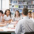 Schoolchildren and teacher studying in school library — Stock Photo