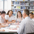 Schoolchildren and teacher studying in school library — Stock Photo #4761243
