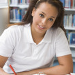 Student studying in library — Stockfoto