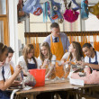 Schoolchildren and teacher sitting around a table in art class — Stock Photo