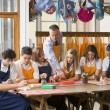 Schoolchildren and teacher sitting around a table in art class — Stock Photo #4761320