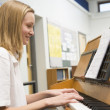 Schoolgirl playing piano in music class — Stock Photo #4761346