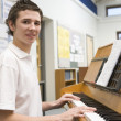 Schoolboy playing piano in music class — Stock Photo