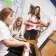 Schoolgirls playing musical instruments in music class - Stok fotoğraf