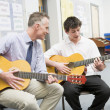 Schoolboy and teacher playing guitar in music class — Stock Photo