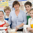Schoolchildren and teacher at school in a cooking class - Stock Photo
