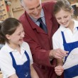 Stock Photo: Schoolgirls and teacher in woodwork class