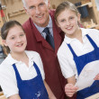 Schoolgirls and teacher in woodwork class - Stock Photo