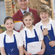 Schoolchildren and teacher in woodwork class - Stock Photo