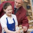 Schoolgirl and teacher in woodwork class - Stock Photo