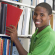 University student choosing book in library — Foto Stock