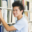University student selecting book from library shelf — Stock Photo