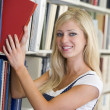 University student selecting book from library — Stock Photo #4761458