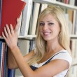 Stock Photo: University student selecting book from library