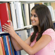 University student selecting book from library — Stock Photo