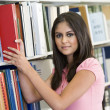 University student selecting book from library — Stock Photo #4761462