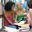 Three students working together in library - Stockfoto