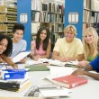 Group of university students working in library -  