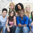 Group of university students sitting on steps - Stock Photo