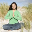 Young woman meditating amongst sand dunes - Stockfoto