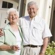 Senior couple standing outside house — Stock Photo #4762263