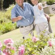 Stock Photo: Grandfather and grandson outdoors in garden pointing at plants a