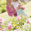 Stock Photo: Grandmother and granddaughter outdoors in garden smiling