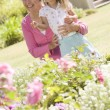 Grandmother and granddaughter outdoors in garden smiling - Stock Photo