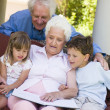 Stock Photo: Grandparents reading to grandchildren