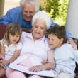Grandparents reading to grandchildren - Stock Photo