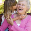 Grandmother getting a kiss from granddaughter — Stock Photo #4763488