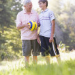 Grandfather and grandson at a park holding a ball and smiling — Stock Photo