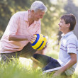Grandfather and grandson at a park with a ball smiling — Stock Photo